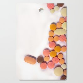 Numerous colorful pills on white background. Cutting Board