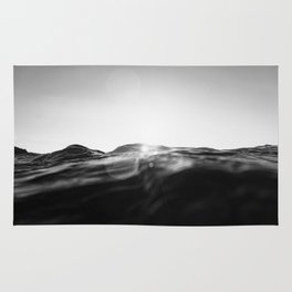 monochromatic sea swell at sunset Rug