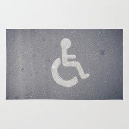 Wheelchair sign icon on asphalt gray street road Rug