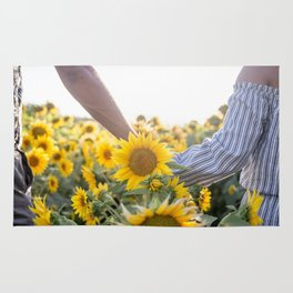Couple holding hands in a sunflower field Rug
