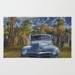 Vintage Blue Plymouth Automobile against Palm Trees and Cloudy Blue Sky near Palm Springs California Rug