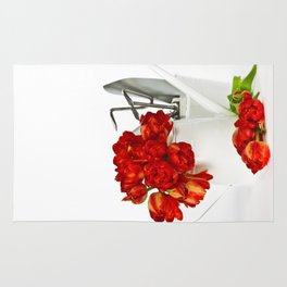 Fresh red tulips in white watering can and garden tools Rug
