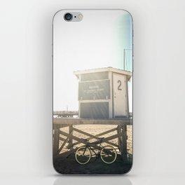 Bike leaning against lifeguard hut on beach iPhone Skin