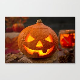 Burning Jack O'Lantern on a rustic table with autumn decorations Canvas Print