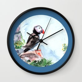 Puffin sitting on a rock with a blue background Wall Clock
