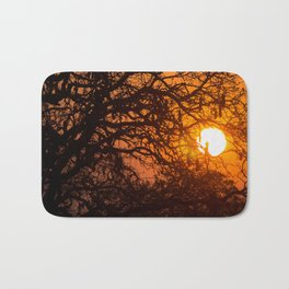 Sultry sun setting behind the sausage tree Bath Mat