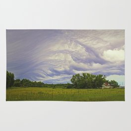 Storm rolling over small farm Rug