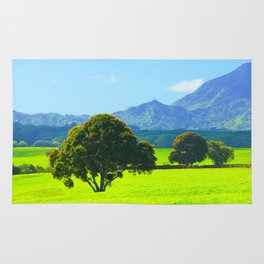 green tree in the green field with green mountain and blue sky background Rug