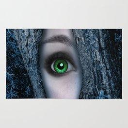 Big green eye in a blue tree Rug