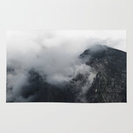 White clouds over the dark rocky mountains Rug