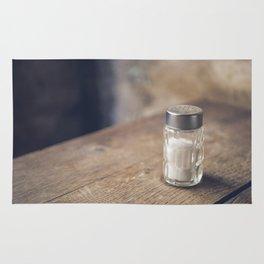 Salt shaker on a table kitchen food background Rug