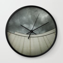 Building with metal covering against stormy sky Wall Clock