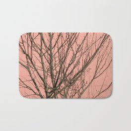 Bare tree against a pink wall Bath Mat