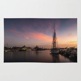 Sailboat moored in Long Beach at sunset Rug