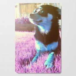 Blue dog on pink grass. Cutting Board