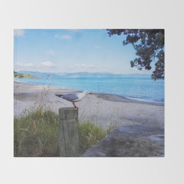 bird on pole waiting in new zealand water front Throw Blanket