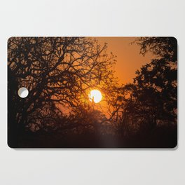 Sultry sun setting behind the sausage tree Cutting Board