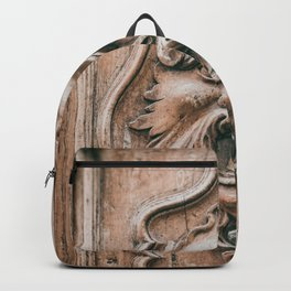Face with beard carved on ancient door in Pisa Tuscany Italy Backpack