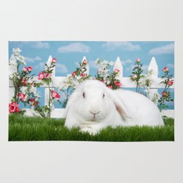 White lop eared bunny in a flower garden Rug
