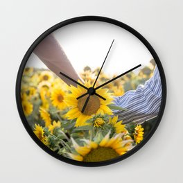 Couple holding hands in a sunflower field Wall Clock