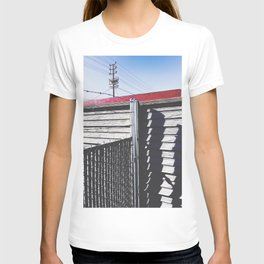 steel fence and wooden fence with red building in the city T-shirt