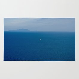 Boat in the blue sea Rug