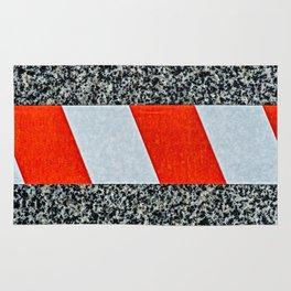 Red warning tape across granite stone Rug
