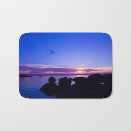 Blue sunset by rock beach Bath Mat